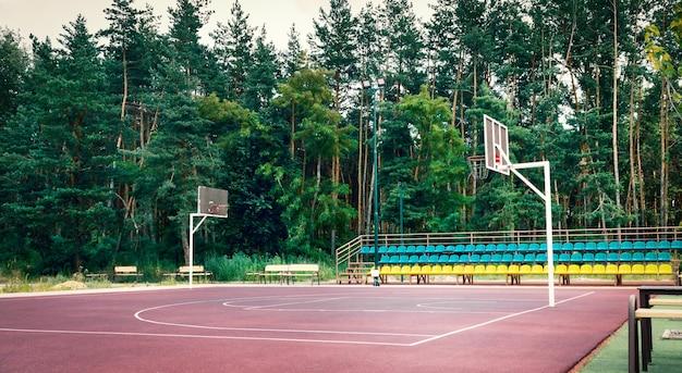 숲 근처 스포츠 단지에 야외 공공 농구 코트.