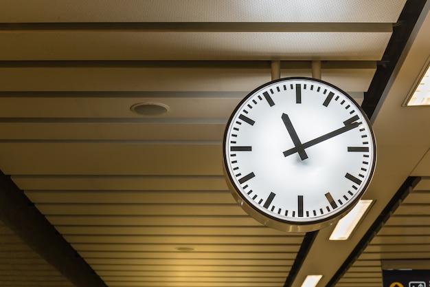 Общественные большие белые часы на железнодорожной станции