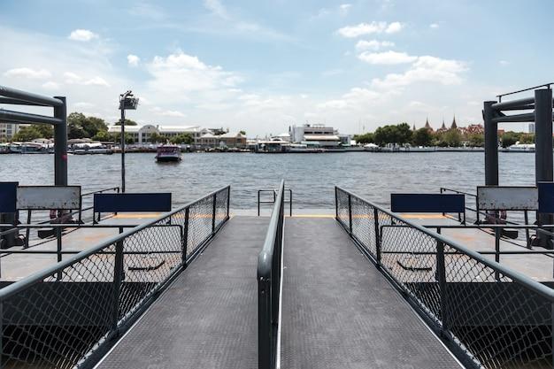 川でドッキングしているボートを降りる乗客のためのタイのバンコクの公共ボートステーション