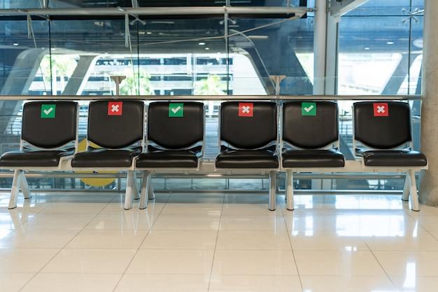 空港ターミナルでのcovid-19の状況の間、社会的に間隔を空けた公共の椅子のレイアウト。社会的距離の概念。