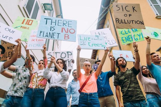 Общественная демонстрация на улице против глобального потепления и загрязнения. группа многонациональных людей, протестующих против изменения климата и пластических проблем в океанах