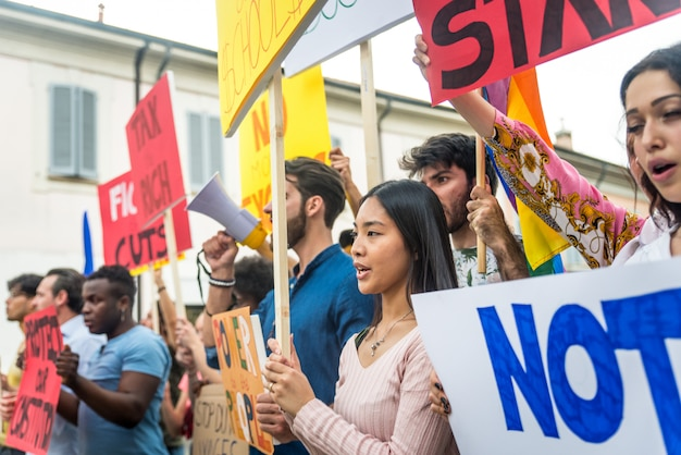 Public demonstration on the street against social problems and human rights. group of multiethnic people making public protest