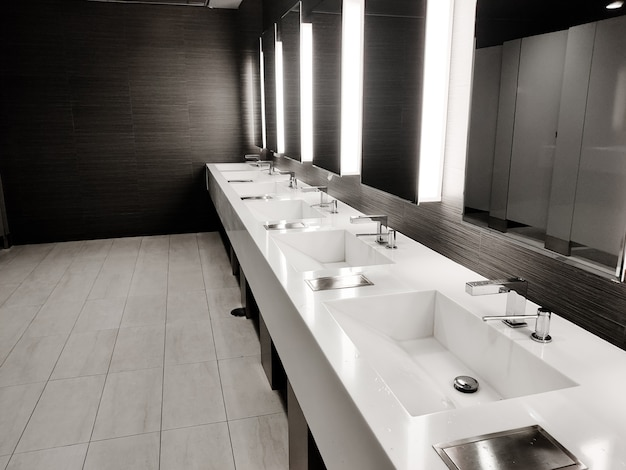 Public empty restroom with washstands, baby changer, and toillets in mirror. white sink row with mirrors and lights. top horizontal view copyspace