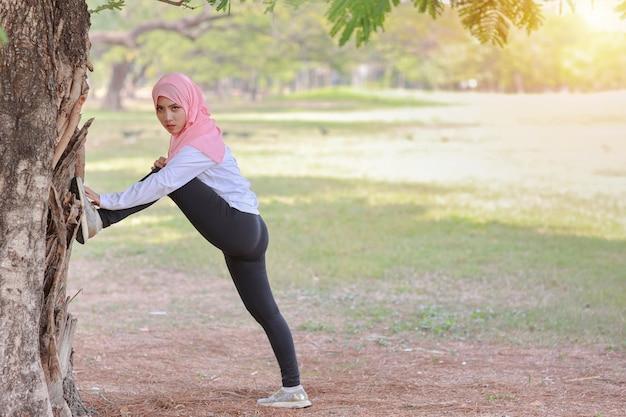 公共運動ライフスタイルのコンセプト、ワイヤレスイヤホンや携帯電話から音楽を聴くフィットネス女性。スポーツウェアの立っている、トレーニング後にストレッチの側面図アスレチック若いアジアのイスラム教徒の少女
