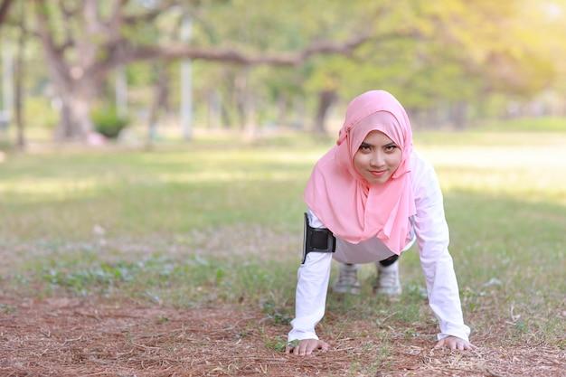 公共運動ライフスタイルのコンセプト、ワイヤレスイヤホンや携帯電話から音楽を聴くフィットネス女性。トレーニング後に腕立て伏せをしているスポーツウェアの若いアジアのイスラム教徒の少女