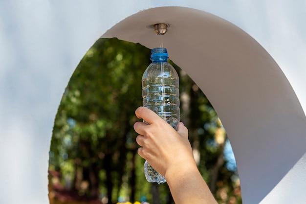 Общественный фонтанчик с бесплатной питьевой водой. женщина наливает воду в бутылку