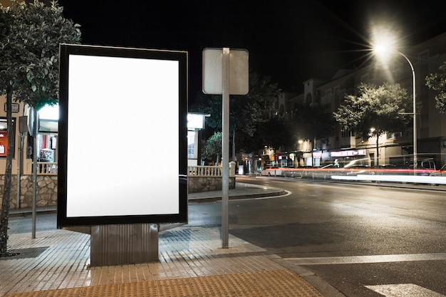 Public information board with blurred vehicles lights in city