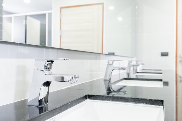 Public interior of bathroom with sink basin faucet lined