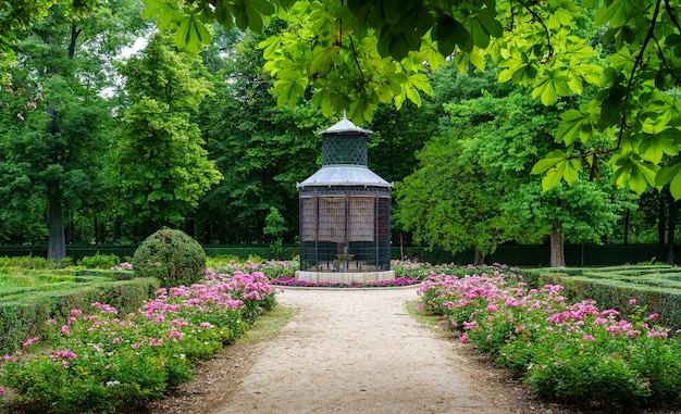 봄에 대형 새장과 꽃 울타리가있는 공원 코너