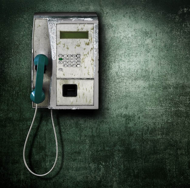 Public phone on green background