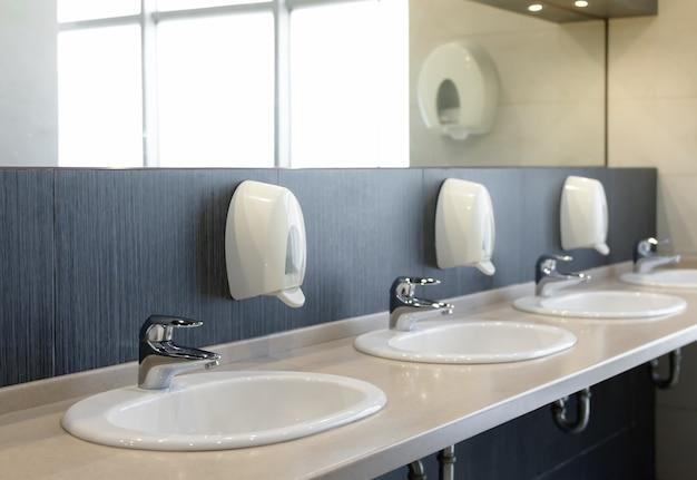 シンクの蛇口と鏡付きの公衆トイレ。浅い被写界深度