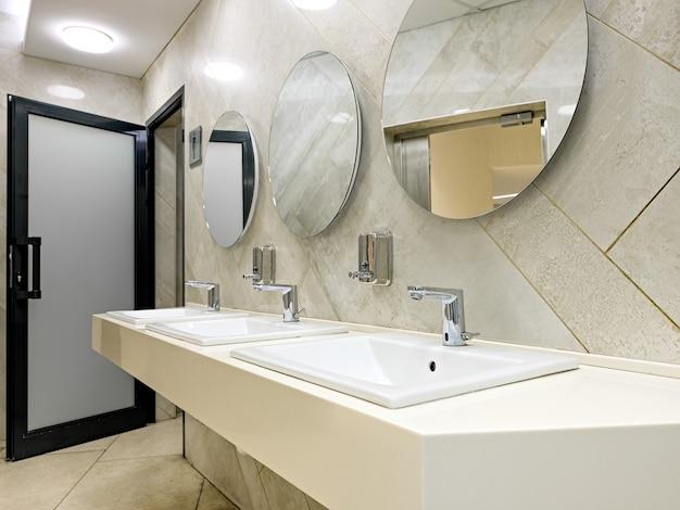 세면대 수도꼭지와 거울이 있는 공중 화장실.