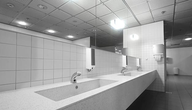 シンクの蛇口と鏡のある公衆トイレ