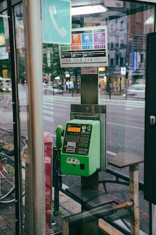 ガラスパネルの後ろの街の公衆電話