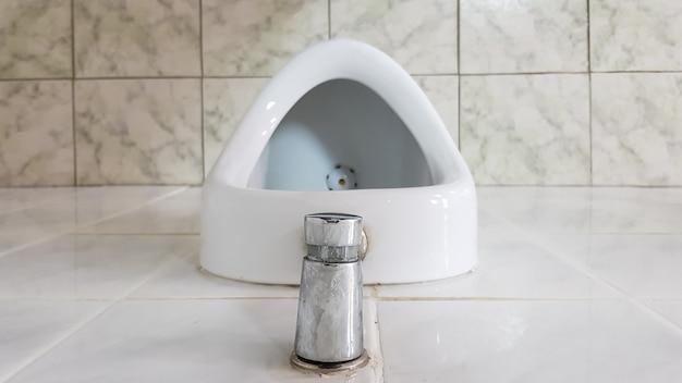 セラミック小便器1つ付きの公衆トイレ。小便器は男性用のボウルを用意します。