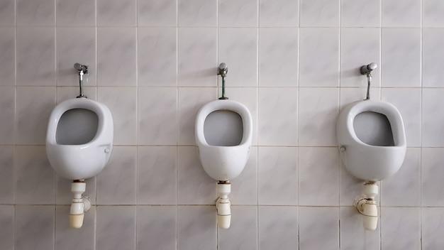 セラミック小便器がたくさんある公衆トイレ。大きな公衆トイレ、トイレに壁に取り付けられたボウル。小便器は男性用のボウルを用意します。