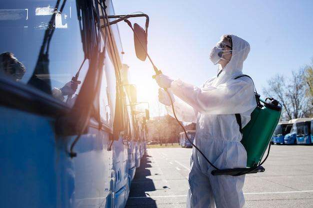 駐車中のバスに消毒剤を噴霧する貯水池を備えた白い防護服を着た公共交通機関の消毒男。コロナウイルスまたはcovid-19を停止します。