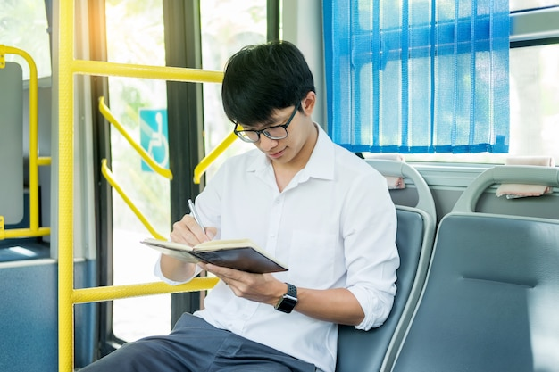 Public transportation, mobility. handsome young businessman reading book on bus