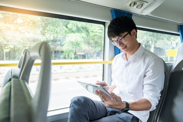 公共交通機関、モビリティ。バスでハンサムな若い実業家の読書