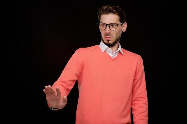眼鏡をかけた若いあごひげを生やした男が拒否ジェスチャーをし、嫌悪感を持って見る