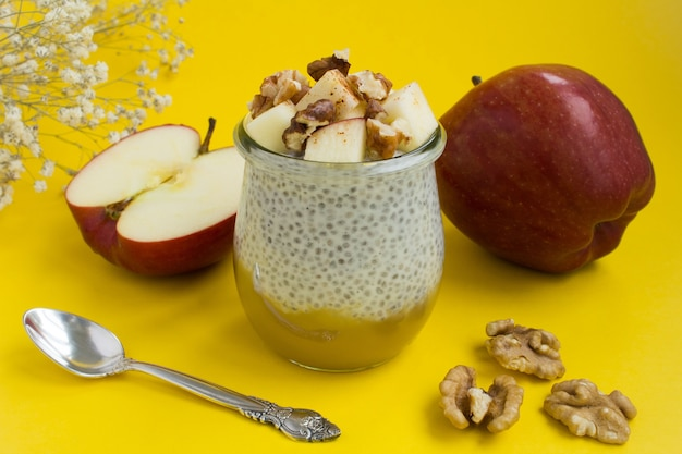 Pudding with chia, apples,cinnamon and walnuts on the yellow background