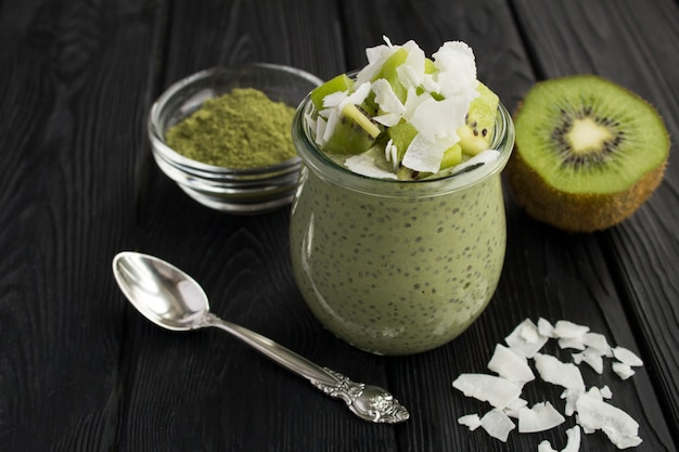 Pudding with chia, matcha tea, kiwi and coconut flakes in the glass jar on the black wooden