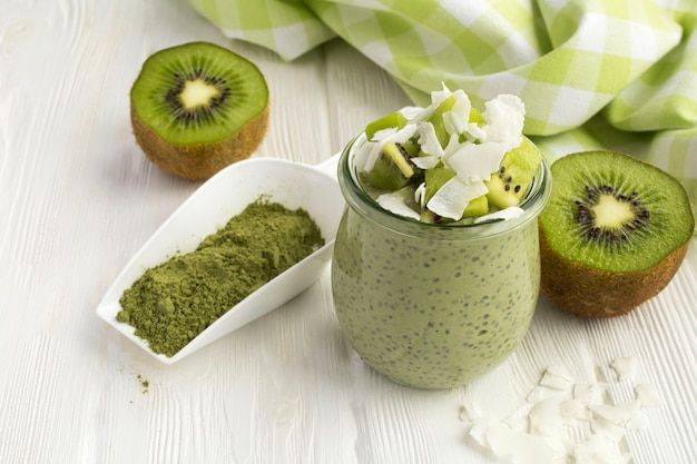 Pudding with chia, matcha tea, kiwi and coconut flakes in the glass jar