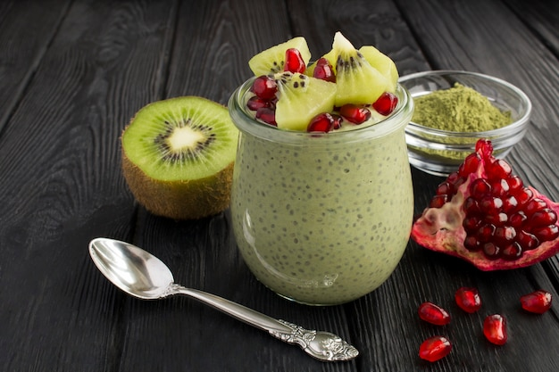 Pudding with chia, matcha tea, kiwi and pomegranate seeds in the glass jar on the black wooden background