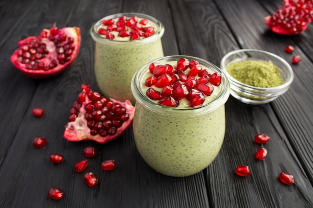 Pudding with chia, matcha tea and pomegranate seeds in the glass jars