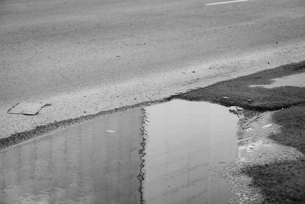 Puddle on road in grayscale. building wall reflected on water in rainy weather close up. apathy, depression, sorrow atmosphere in russia. garbage on asphalt.