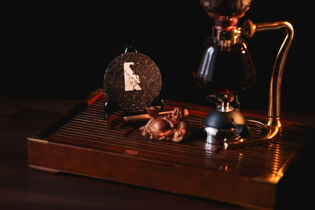 Puer tea in the siphon with extruded pancake shu puer and buddha statue