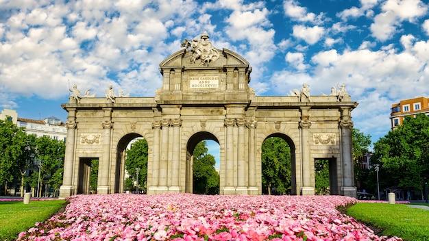 푸에르타 데 알칼라 데 마드리드(puerta de alcala de madrid)는 지상에 꽃이 피어 있고 화창한 날에는 흰 구름이 있습니다.