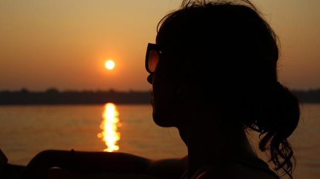 Puerto maldonado ãƒâ'ã'â»; august 2017: a girl on a sunset from the madre de dios river