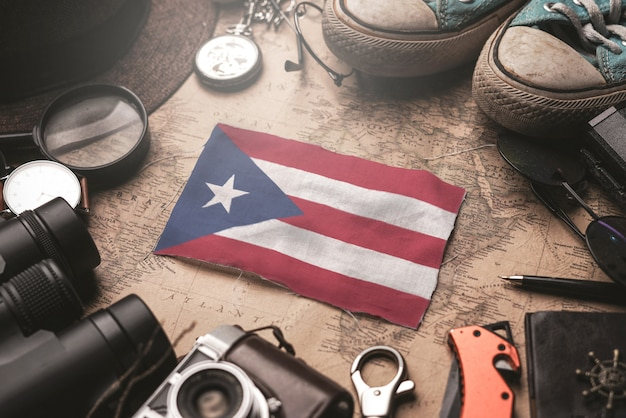 Puerto rico flag between traveler's accessories on old vintage map. tourist destination concept.