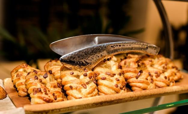 Слоеные булочки, косички, орехи в ряд, в лотке на прилавке, с металлическими щипцами