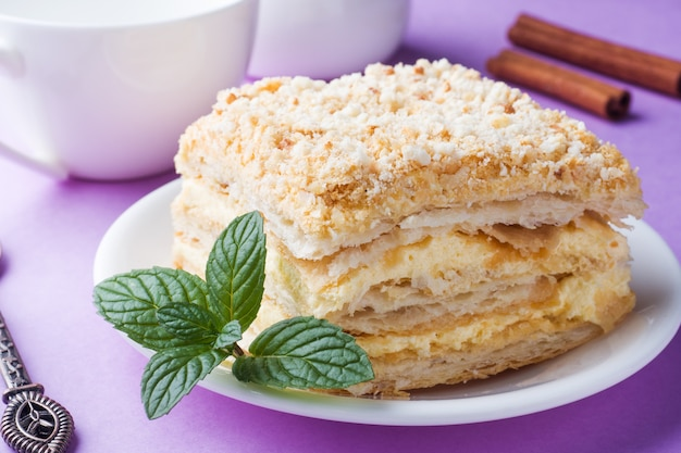 Puff cake with cream napoleon millefeuille vanilla slice with mint color on purple background.