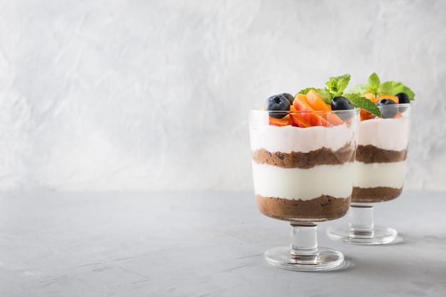 Puff dessert made of chocolate biscuit, cream cheese garnished with fresh apricot.