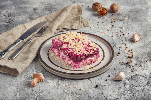 Puff fish salad of herring, beets, potatoes with mayonnaise, russian cuisine, light background