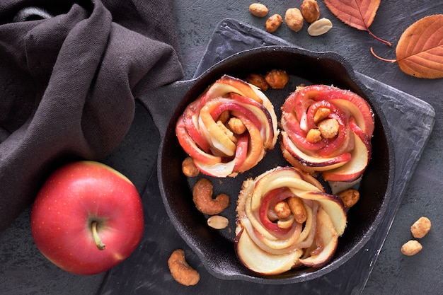 Puff pastries with rose shaped apple slices baked in cast iron skillet and fresh red apple