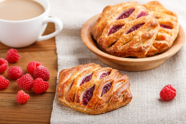 Puff pastry buns with strawberry jam on wooden background with linen textile and a cup of coffee