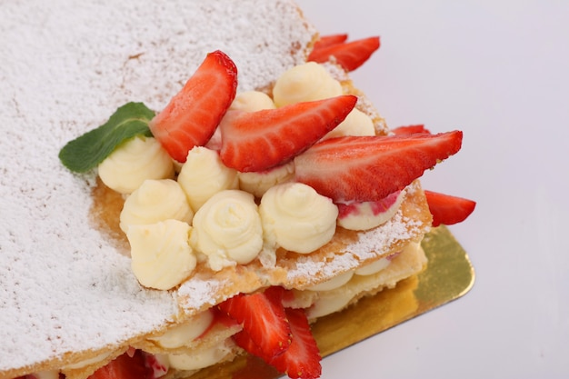 Puff pastry cake with cream decorated with strawberries