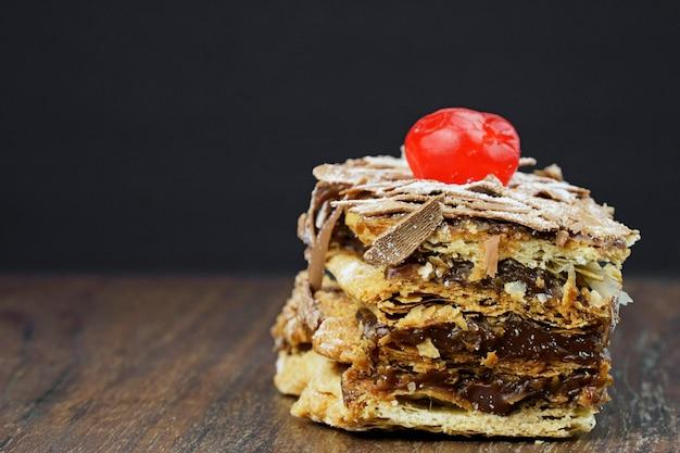 나무 테이블에 가루 설탕과 초콜릿 크림을 넣은 퍼프 페이스트리 케이크. 텍스트를 위한 공간을 닫습니다. 선택적 초점입니다.