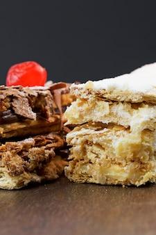 슈가파우더와 크림을 얹은 퍼프 페이스트리 케이크와 나무 테이블 위에 초콜릿과 체리를 얹은 또 다른 케이크. 텍스트를 위한 공간을 닫습니다. 선택적 초점입니다. 수직의.