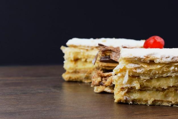 슈가파우더와 크림을 얹은 퍼프 페이스트리 케이크와 나무 테이블 위에 초콜릿과 체리를 얹은 또 다른 케이크. 텍스트를 위한 공간을 닫습니다. 선택적 초점입니다.