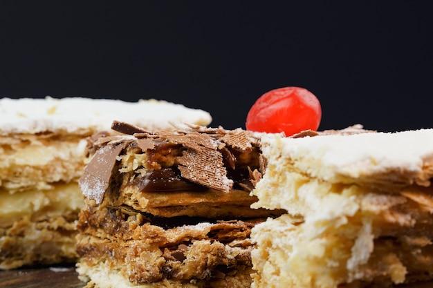 슈가파우더와 크림을 얹은 퍼프 페이스트리 케이크와 나무 테이블 위에 초콜릿과 체리를 얹은 또 다른 케이크. 확대. 선택적 초점입니다.