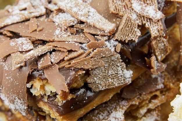 슈가파우더와 크림을 얹은 퍼프 페이스트리 케이크와 나무 테이블 위에 초콜릿과 체리를 얹은 또 다른 케이크. 매크로를 닫습니다. 선택적 초점입니다.