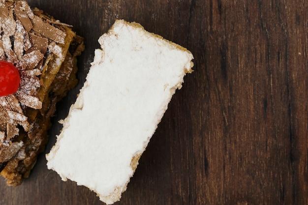 슈가파우더와 크림을 얹은 퍼프 페이스트리 케이크와 나무 테이블 위에 초콜릿과 체리를 얹은 또 다른 케이크. 상위 뷰 및 텍스트를 위한 공간입니다. 선택적 초점입니다.