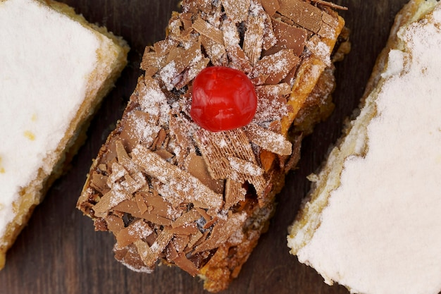 슈가파우더와 크림을 얹은 퍼프 페이스트리 케이크와 나무 테이블 위에 초콜릿과 체리를 얹은 또 다른 케이크. 평면도. 선택적 초점입니다.