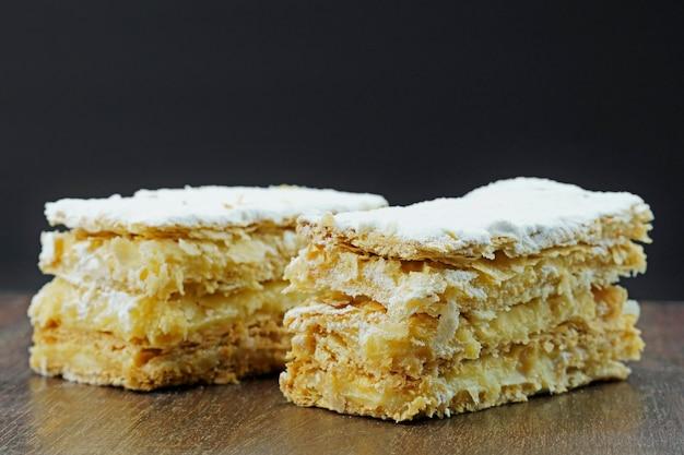 나무 테이블에 가루 설탕과 크림을 넣은 퍼프 페이스트리 케이크. 텍스트를 위한 공간을 닫습니다. 선택적 초점입니다.