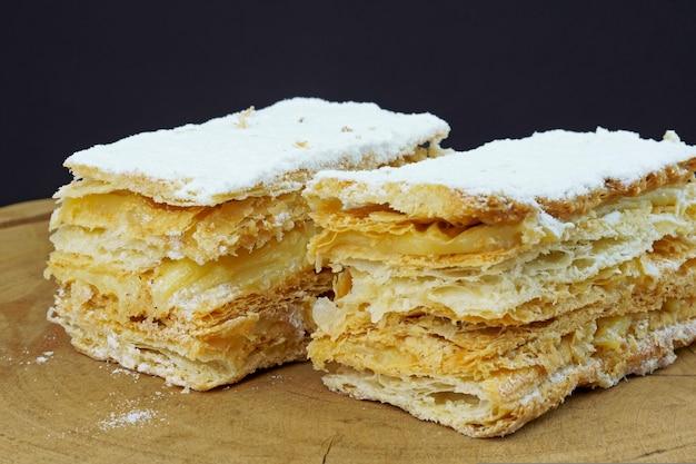 나무 판자에 슈가파우더와 크림을 얹은 퍼프 페이스트리 케이크. 선택적 초점입니다.